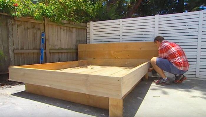 Мужчина строит кровать посреди двора.
