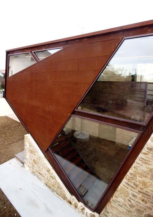 Переход между зданиями выполнен из кортеновской стали и стекла.