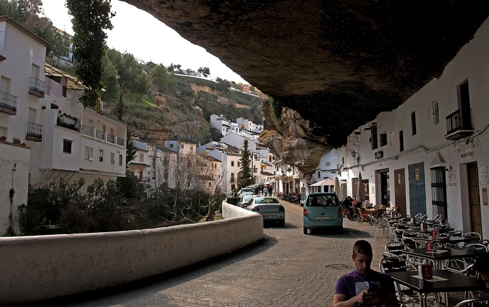 Улица, проходящая под скалой.