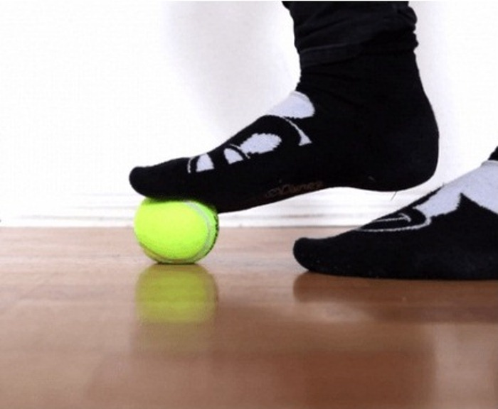 Упражнение для стопы с теннисным мячом.