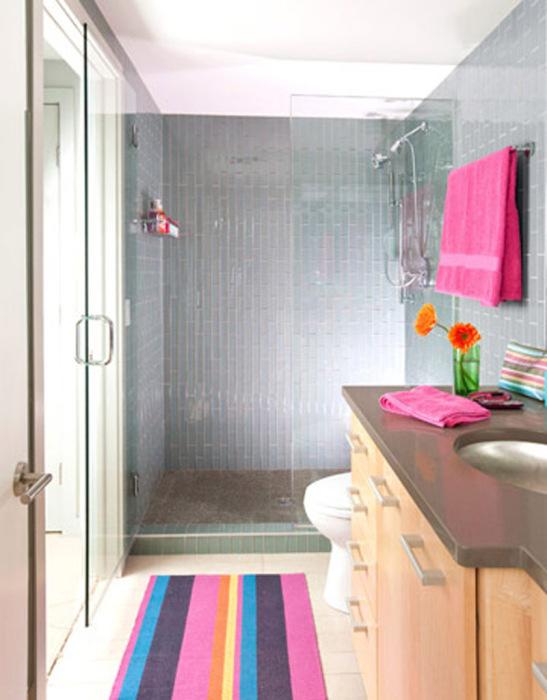 Яркие полотенца и коврик привносят колорит в интерьер ванной комнаты.