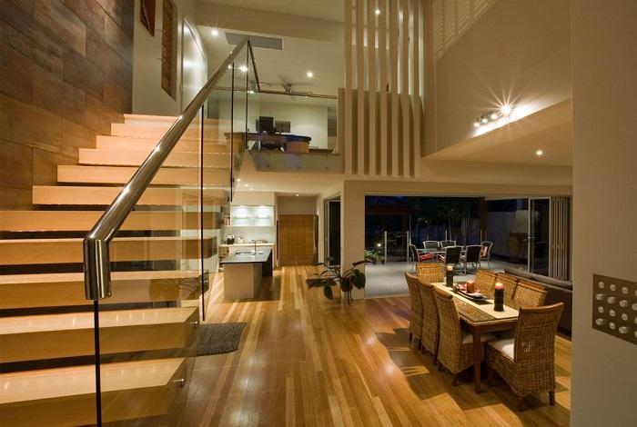 Современная лестница с традиционными деревянными ступенями и прозрачными перилами из стекла.