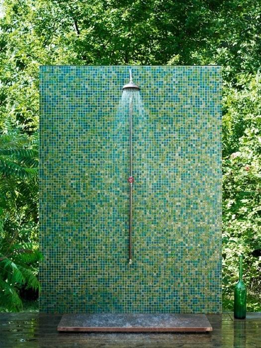 Летний душ, который сливается с растительностью на дачном участке.