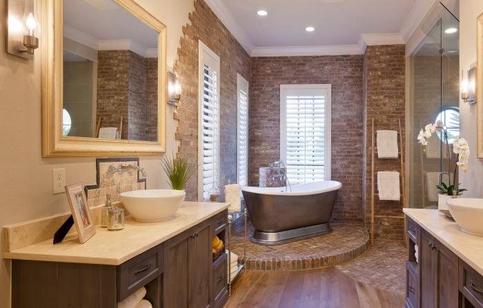 Чудесная ванная комната приятного бежевого оттенка с округлой ванной и декоративной плиткой.