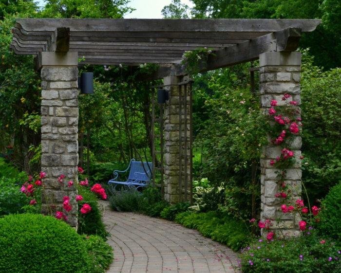 Деревянные арки с каменным основанием набирают популярность при оформлении ландшафтного дизайна в различных стилях.