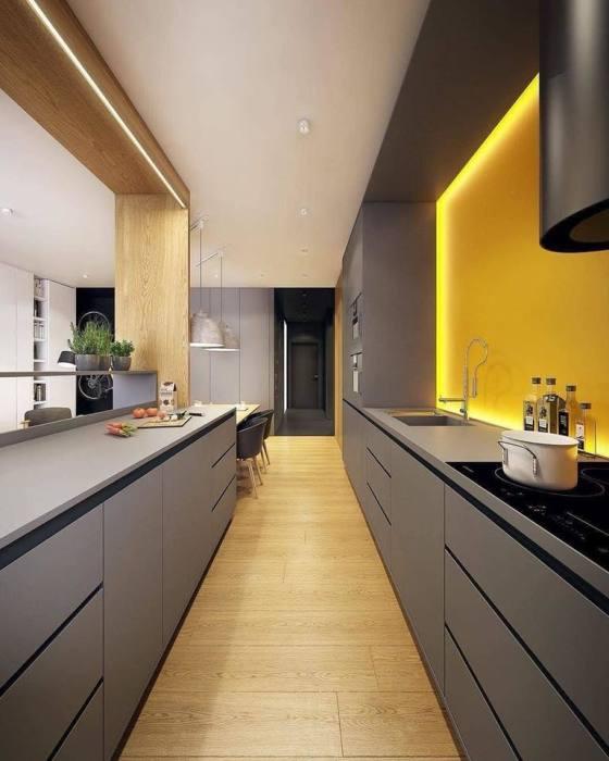 Просторная современная кухня, оформленная в стиле хай-тек, с эргономичными серыми шкафчиками и стенкой ярко-оранжевого цвета.