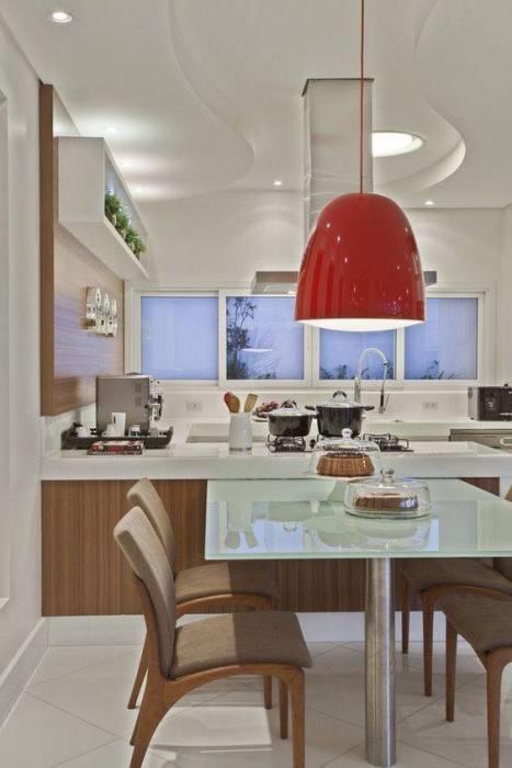 Кухня с комфортной обеденной зоной, мягкой мебелью и ярким светильником красного цвета.