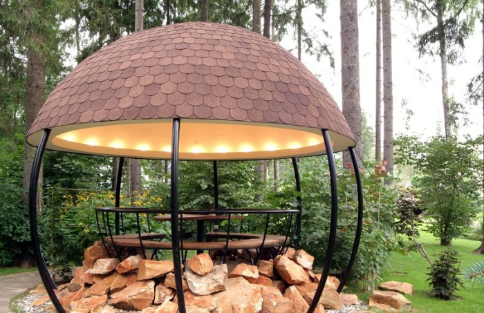 Фантастическая беседка открытого типа в форме полусферы, сделанная из металлических труб, дерева и камня - нестандартное и очень красивое решение, которое впишется в любой современный дачный участок.