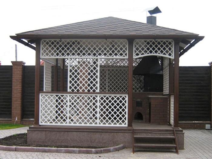 Беседка открытого типа с зоной для барбекю, построенная исключительно из натуральной тёмной древесины станет уникальным украшением дачного участка.