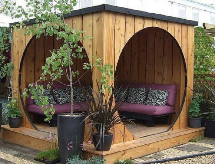 Современная деревянная беседка с двумя круглыми дверными проёмами и мягким угловым диванчиком станет уютным местом для отдыха и настоящим украшением любого дачного участка.