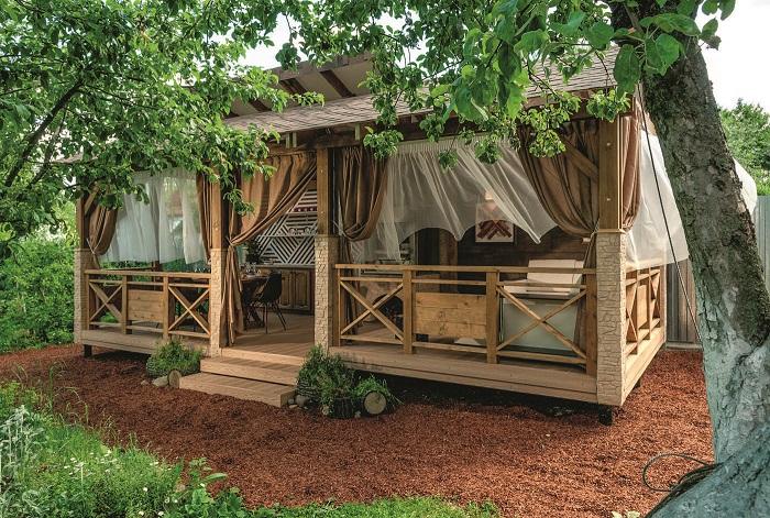 Классическая деревянная беседка с мангалом и местом для ужина, которая совмещает приватность и комфорт.
