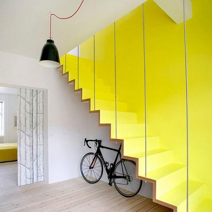 Лестница лимонного цвета, которая сливается с контрастной стеной того же оттенка.