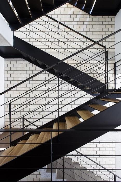 Кованый металл и недорогая древесина — популярное сочетание для обустройства традиционной лестницы.