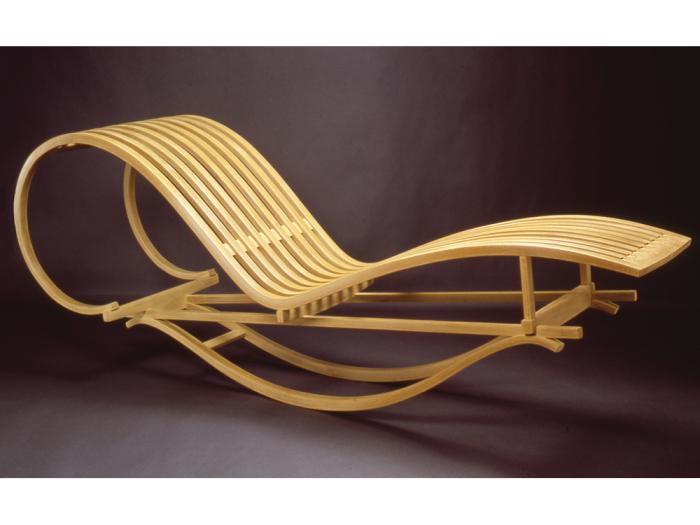 Качалка-шезлонг с плавными формами, выполненная из натурального красного дерева.