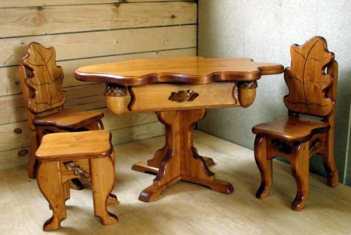 Комплект мебели из массива дерева, декорированный резными желудями и спинками в виде дубовых листьев.
