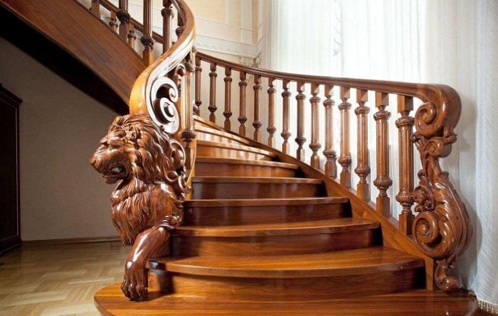Элегантная деревянная лестница с объемными резными столбами и балясинами в виде рычащего льва.