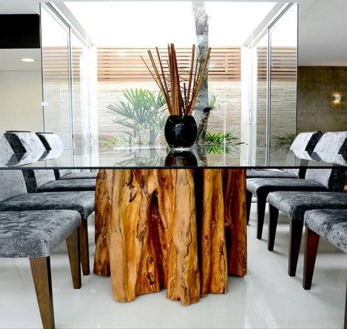 Обеденный стол из стекла и массивного ствола дерева станет главным украшением комнаты.