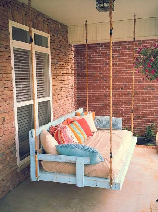 Подвесной диван для открытой веранды, который можно сделать из старых деревянных поддонов.