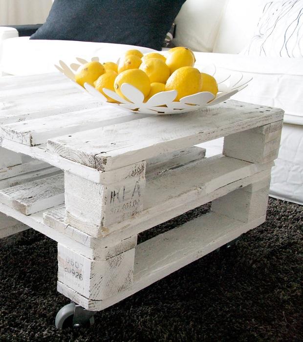 Белый журнальный столик из деревянных паллетов в интерьере гостиной комнаты.