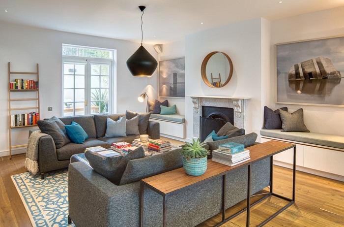 Даже небольшая полка за диваном может стать многофункциональным элементом в интерьере гостиной.