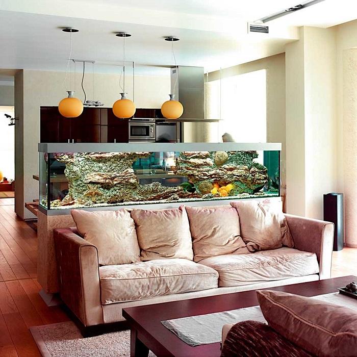 Эффективно задействовать пространство за спинкой дивана можно, разместив здесь аквариум.