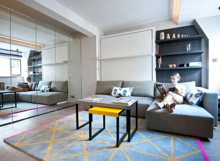 Ниша за диваном, которая служит для размещения многофункциональной модульной стенки.
