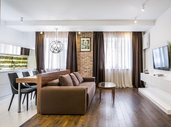 Небольшой обеденный столик из древесины использует пространство за диваном, которое обычно игнорируется.