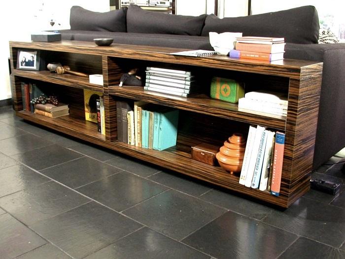 Оформление интерьера гостинной комнаты при помощи комбинирования дивана и небольшого стеллажа.