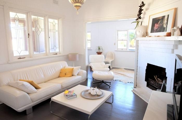 Белый цвет в интерьере поможет визуально увеличить пространство, а камин и мягкое освещение придадут уют.