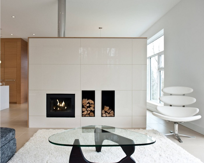 Для просторной гостиной можно применить зонирование с помощью фальшстены со встроенным камином и дровяным хранилищем.