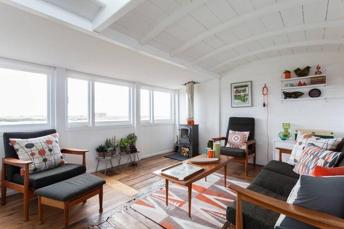 Лаконичный интерьер гостиной можно разбавить подушками и ковриком с колоритным орнаментом.