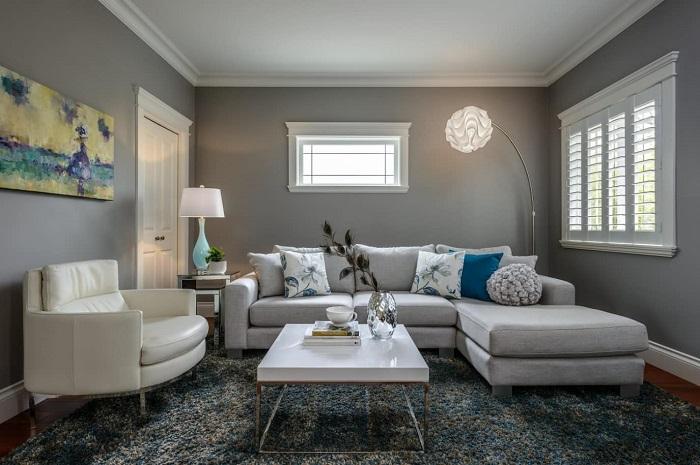 Гостиная в серых тонах будет выглядеть уютней с пушистым ковром и лампами с оригинальным дизайном.