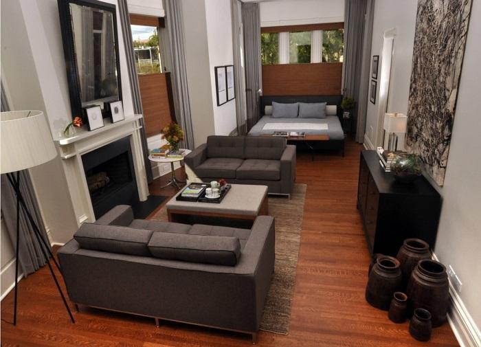 Спальное место в гостиной можно отделить с помощью раздвижных штор, а функциональный сегмент дополнить камином.