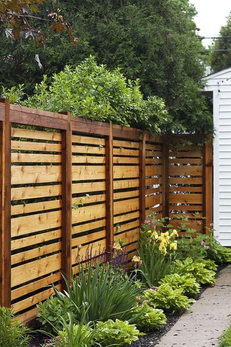 Классическое ограждение из недорогой древесины для небольшого садового участка.