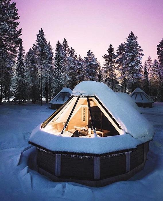 Заснеженный домик с прозрачной крышей в Саариселькя, Финляндия.