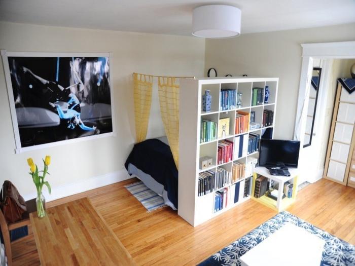 Простой деревянный стеллаж возле спального места, который играет роль перегородки для разделения пространства на функциональные зоны.