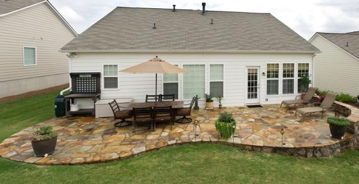 Небольшая площадка для отдыха с уютной плетеной мебелью и небольшим зонтом - оригинальная идея оформления обеденной зоны на придомовой территории.