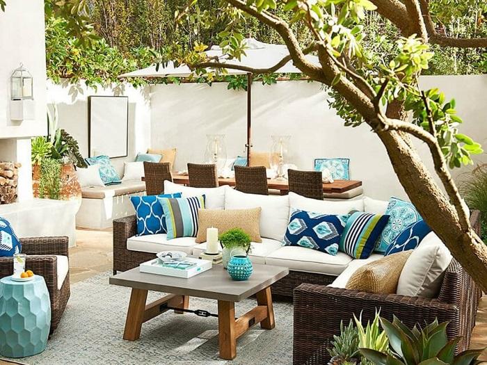 Небольшой деревянный столик, несколько плетеных стульев и дивана, расположенных в тени деревьев на придомовой территории.