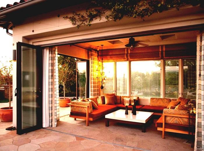 Уютная беседка закрытого типа с большими панельными окнами, облицованная декоративным камнем, выглядит современно и привлекательно.
