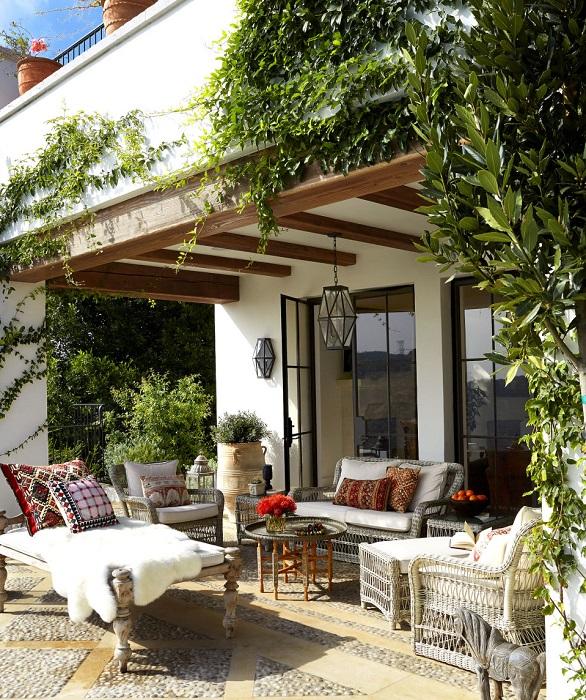 Небольшая площадка с удобной садовой мебелью, декоративными кашпо и журнальным столиком - оригинальная идея для современного загородного участка.