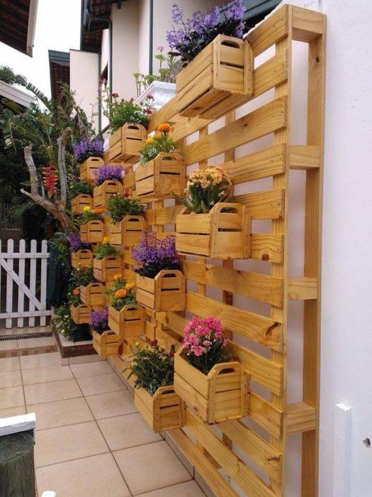 Вертикальный сад из поддонов отлично будет смотреться не только на стене в гостиной, но и на придомовой территории.
