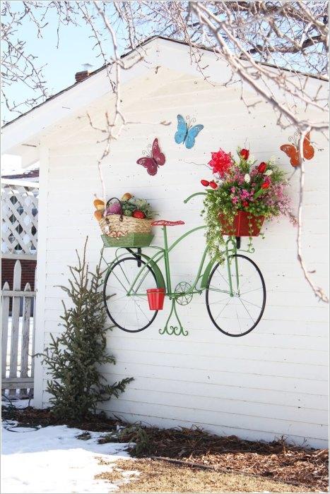 Старый подвесной велосипед, на котором хранятся комнатные цветы.