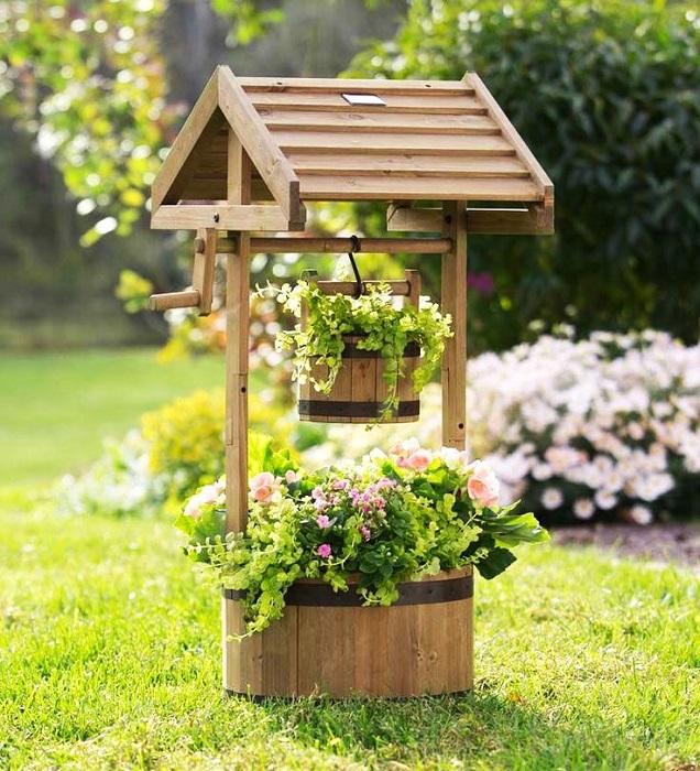 Декоративный колодец, который гармонично вписывается в ландшафтный дизайн садового участка.