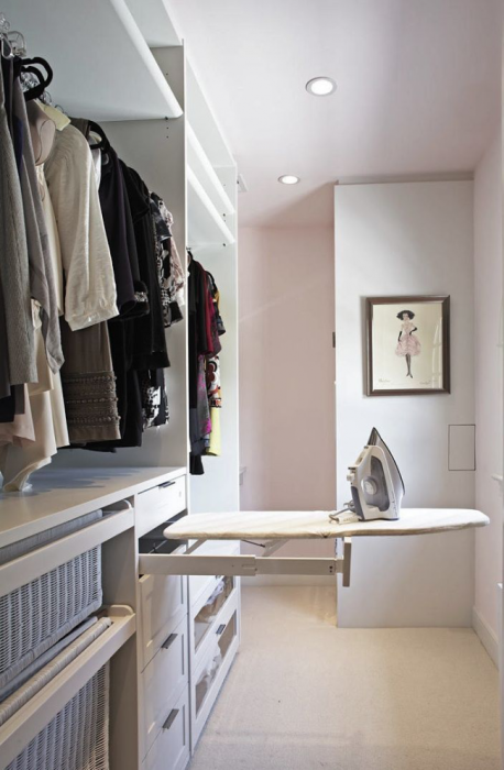 Модульная система с гладильной доской в гардеробном помещении.