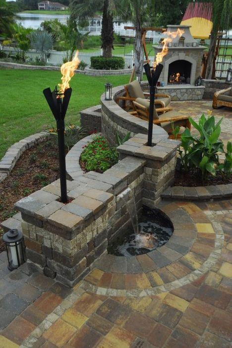 Аккуратное летнее патио, вымощенное тротуарной плиткой, с оригинальным каменным фонтанчиком, удобными креслами и камином.