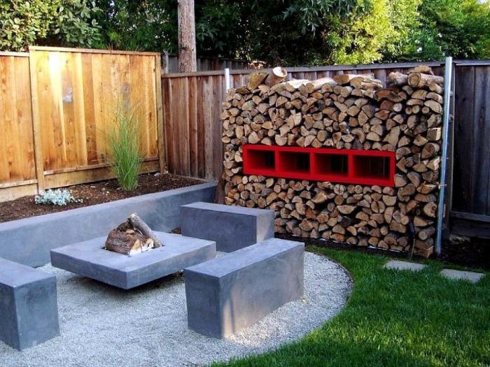 Небольшая площадка для отдыха с компактным угловым бетонным диваном и небольшим очагом.