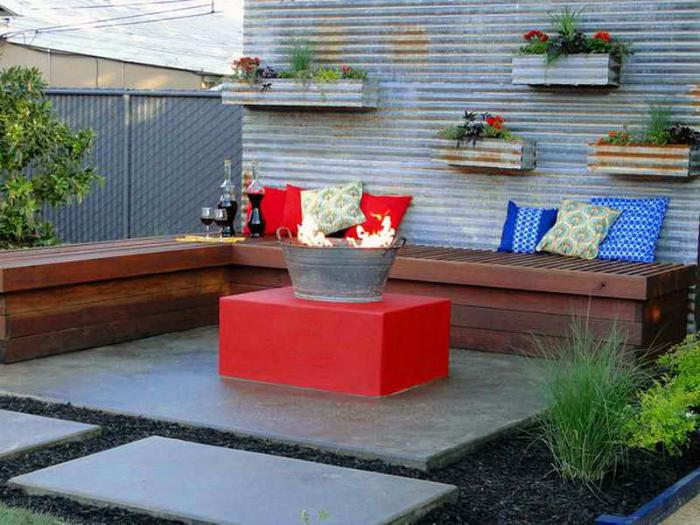 Простое местечко для отдыха с угловой скамейкой из тёмной древесины и оригинальным очагом.