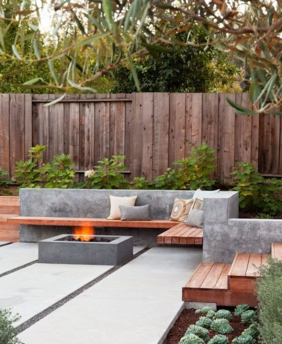 Роскошная площадка с деревянными скамейками, а также же очагом, станет настоящим украшением приусадебного участка.