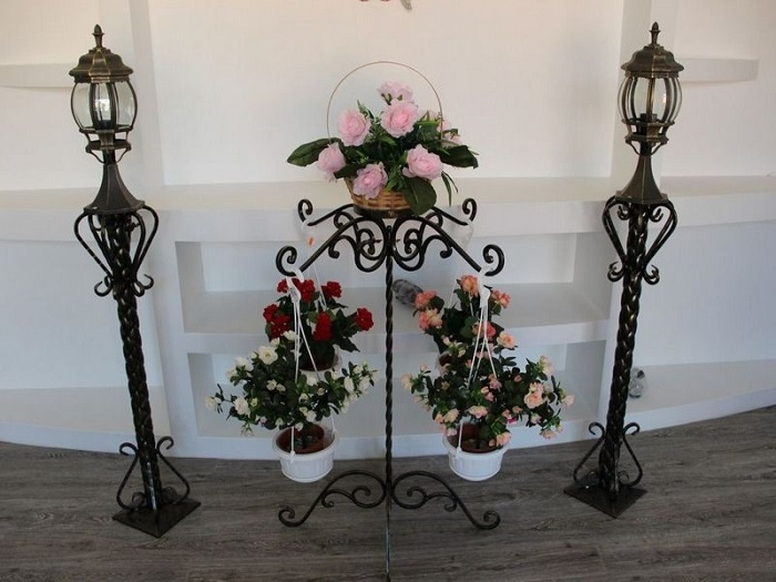 Кованая подставка для цветов и два кованых напольных светильника.