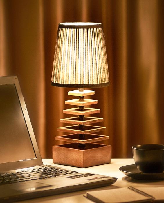 Деревянный настольный светильник-пирамида из древесины ореха с текстильным абажуром.